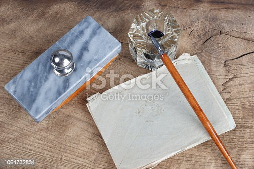 179239584 istock photo Old fountain pen and inkwell with old letters on a wooden background 1064732834