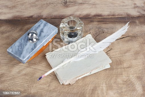 179239584 istock photo Old fountain pen and inkwell with old letters on a wooden background 1064732852