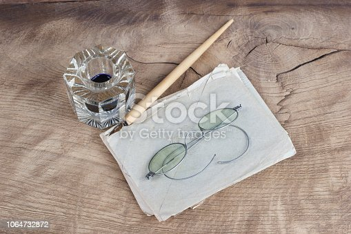 179239584 istock photo Old fountain pen and inkwell with old letters on a wooden background 1064732872