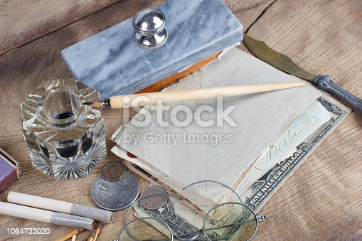 179239584 istock photo Old fountain pen and inkwell with old letters on a wooden background 1064733020
