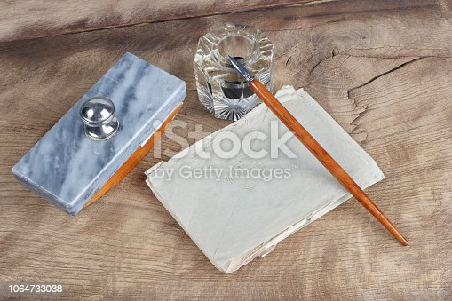 179239584 istock photo Old fountain pen and inkwell with old letters on a wooden background 1064733038