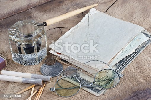 179239584 istock photo Old fountain pen and inkwell with old letters on a wooden background 1064733098