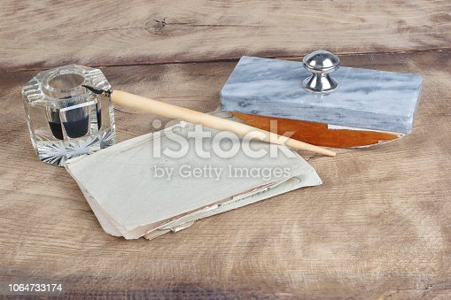 179239584 istock photo Old fountain pen and inkwell with old letters on a wooden background 1064733174
