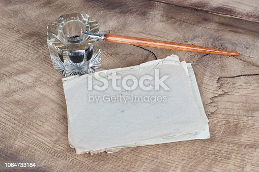 179239584 istock photo Old fountain pen and inkwell with old letters on a wooden background 1064733184