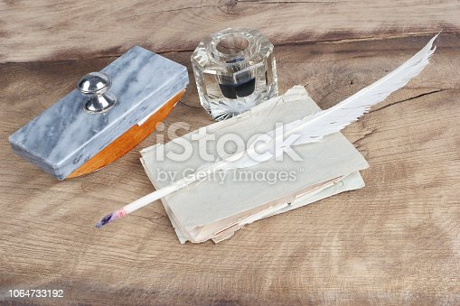179239584 istock photo Old fountain pen and inkwell with old letters on a wooden background 1064733192
