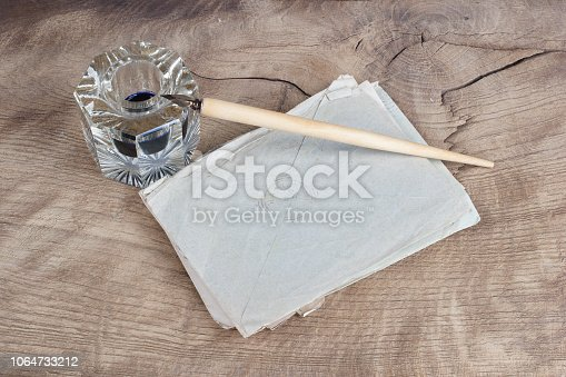 179239584 istock photo Old fountain pen and inkwell with old letters on a wooden background 1064733212