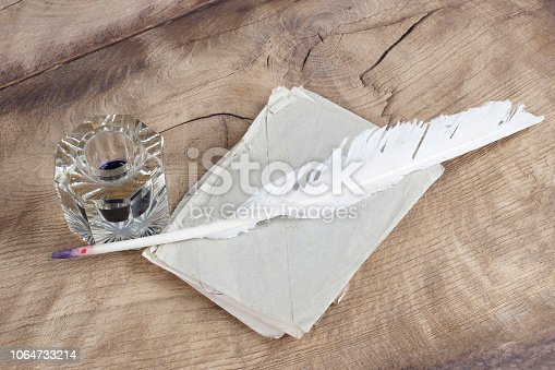 179239584 istock photo Old fountain pen and inkwell with old letters on a wooden background 1064733214