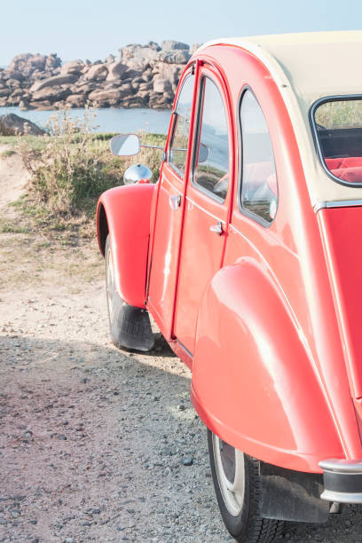 Old Frenc classic 2CV car parked in the dunes near the beach in Brittany, France during a summer vacation stock photo