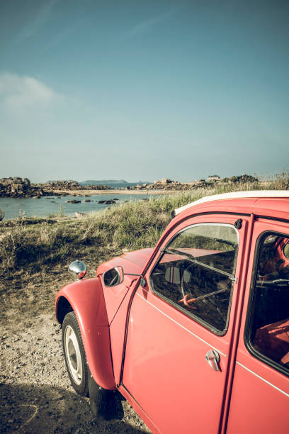 Old French classic Deux Chevaux or Ugly Duckling or car parked in the dunes near the beach in Brittany, France during a summer vacation - foto stock