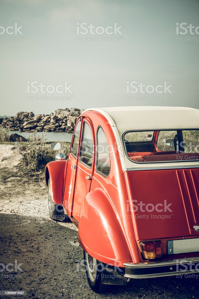 Old French classic Deux Chevaux or Ugly Duckling or car parked in the dunes near the beach in Brittany, France during a summer vacation stock photo