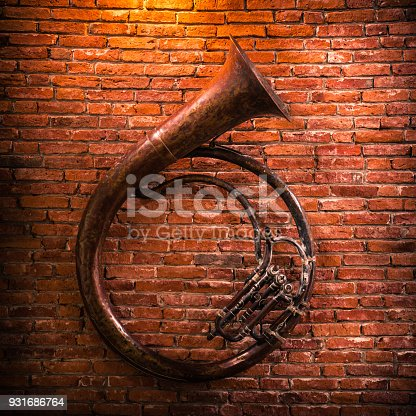 istock Old French horn on brick wall background. 931686764