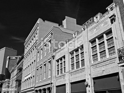 New Orleans, LA USA - May 9, 2018  -  Old French Quarter Buildings with the CBD in B&W Background