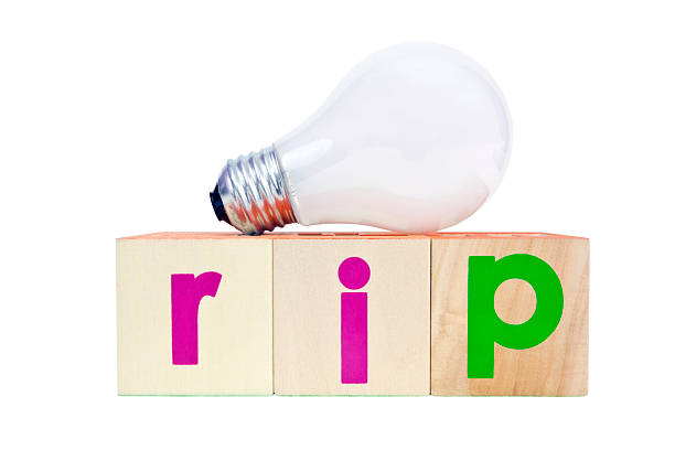 RIP Old Friend Resting in peace...an old friend. The discontinued incandescent lightbulb. Horizontal. anachronistic stock pictures, royalty-free photos & images
