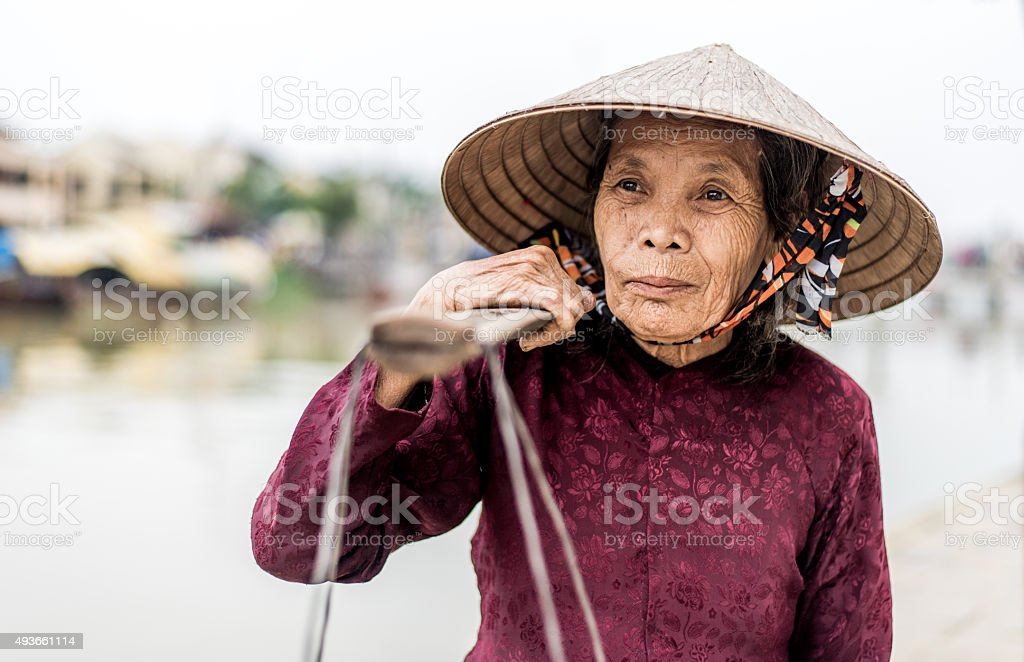 Old friendly woman with vietnamese straw hat stock photo