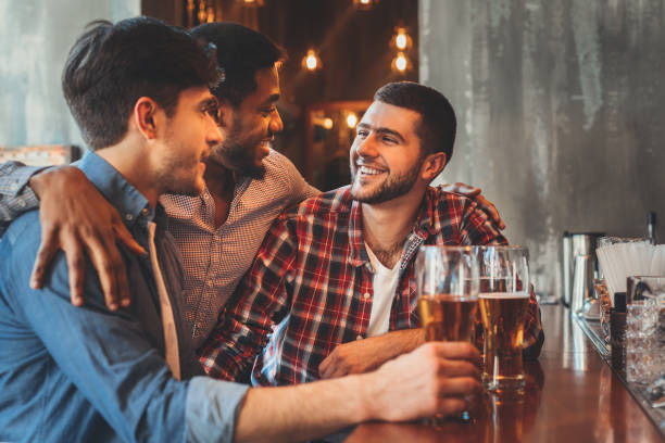 Old friends drinking beer and talking in pub Old friends talking and drinking beer at bar counter in pub bachelor stock pictures, royalty-free photos & images