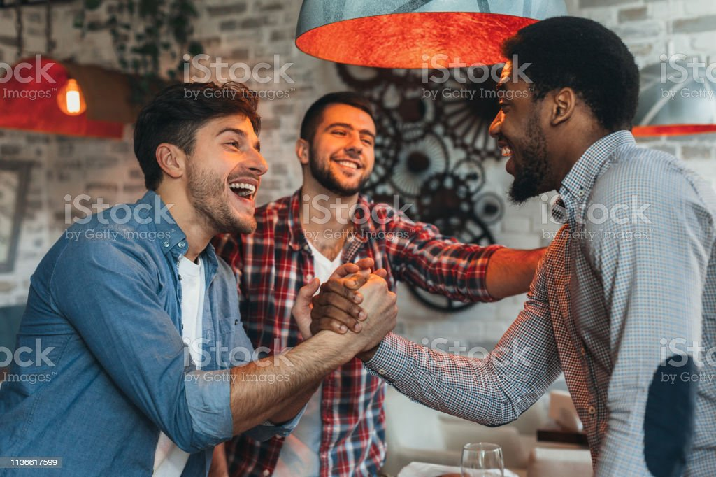 Old friends meeting. Three friends meet in pub Old friends meeting. Three friends meet each other in beer pub Activity Stock Photo