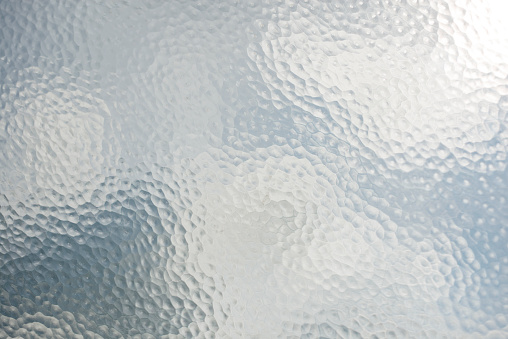 View of cloudy sky through old frosted patterned glass.
