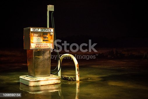 An obsolete fuel pump sits abandoned under an overhang.