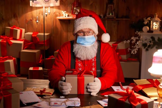 alte lustige bärtige weihnachtsmann trägt gesichtsmaske, halten geschenk-box vorbereitung für weihnachten vorabend sitzen an gemütlichen haustisch spät in der nacht mit geschenken. frohe weihnachten covid 19 coronavirus sichere lieferung. - santa stock-fotos und bilder