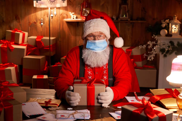 alte lustige bärtige weihnachtsmann trägt gesichtsmaske, halten geschenk-box vorbereitung für weihnachten vorabend sitzen an gemütlichen haustisch spät in der nacht mit geschenken. frohe weihnachten covid 19 coronavirus sichere lieferung. - nikolaus stock-fotos und bilder