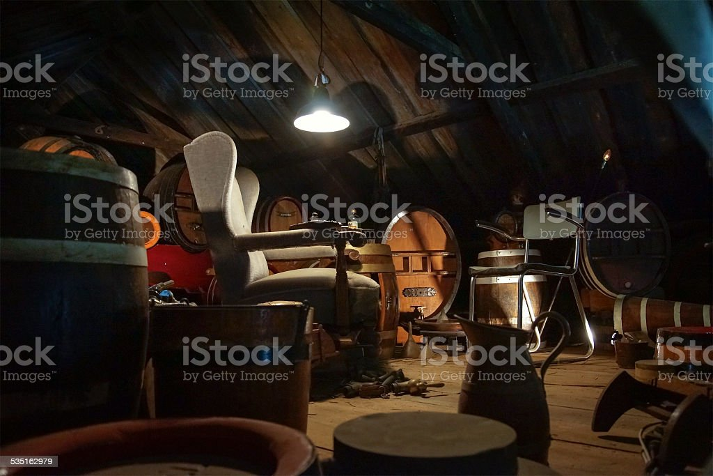 Old furniture on an attic, dimly lit stock photo