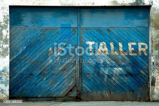 Old garage blue door, closed, paint peeling off. Galicia, Spain.