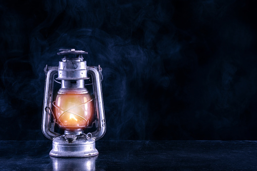 Old gas lantern on black table and foggy and smoke dark and night scenery
