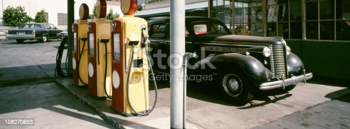 A gas station with 1940s fuel pumps and a vintage car. The photo is shot with a panoramic camera (Hasselbad XPAN), 45mm lens. The image is slightly toned to bring out the reds and yellows of the pumps.