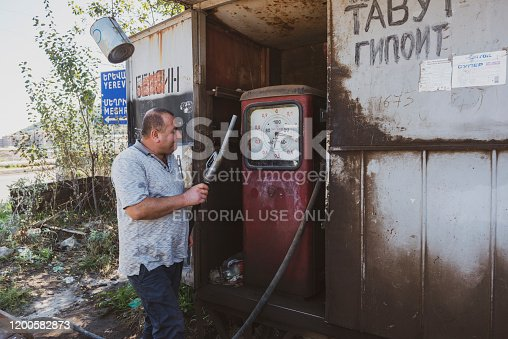 An attendant returns the nozzle to its position after refueling a vehicle at an old gas station in Goris, Armenia
