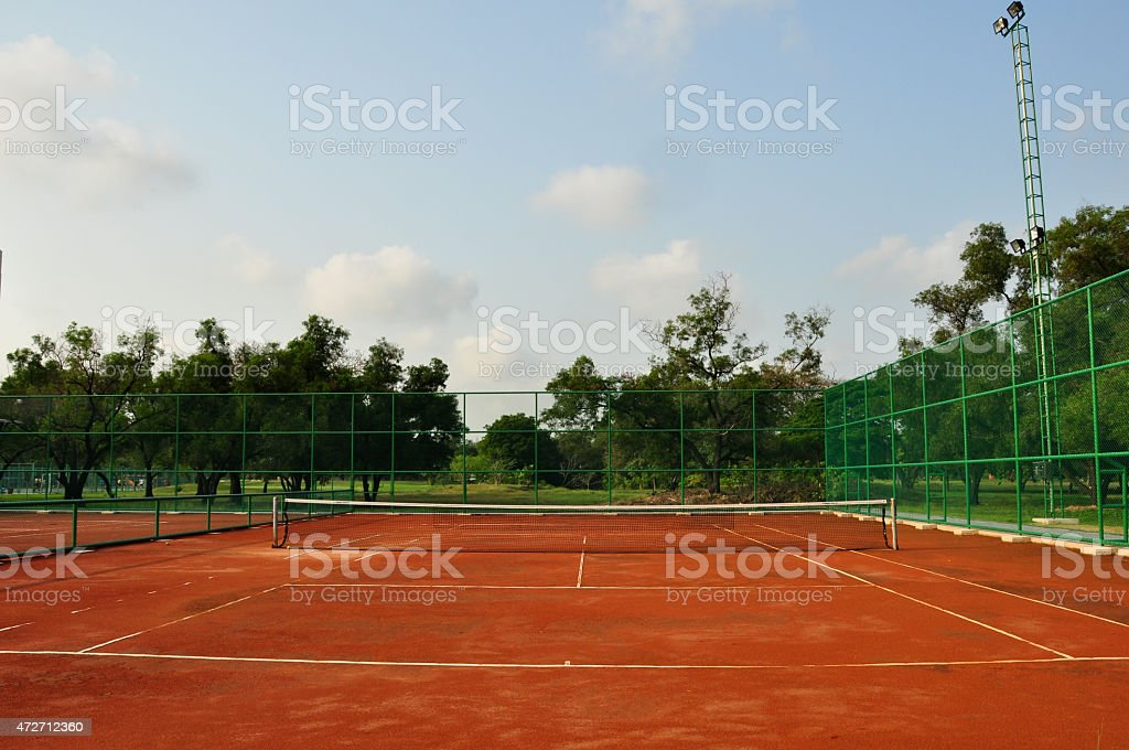Old gated red dirt tennis court stock photo