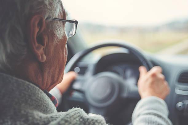 Old gentleman drives car stock photo