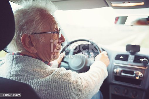 Friendly old gentleman with metal frame glasses drives car