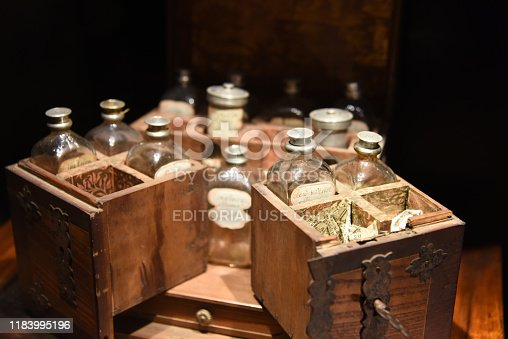 Some really old glass bottles for medical use in a wood box. The image was captured inside of the Muri Abbey in Canton Aargau.