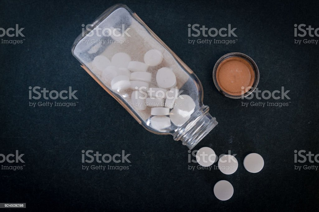 Old Glass Pill Bottle with white pills spilling out stock photo