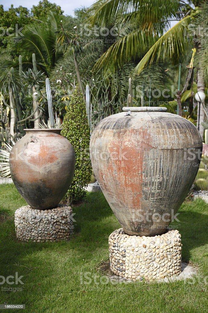 Old glazed water jar in public tropical garden royalty-free stock photo