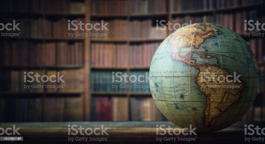 Old globe on bookshelf background. stock photo