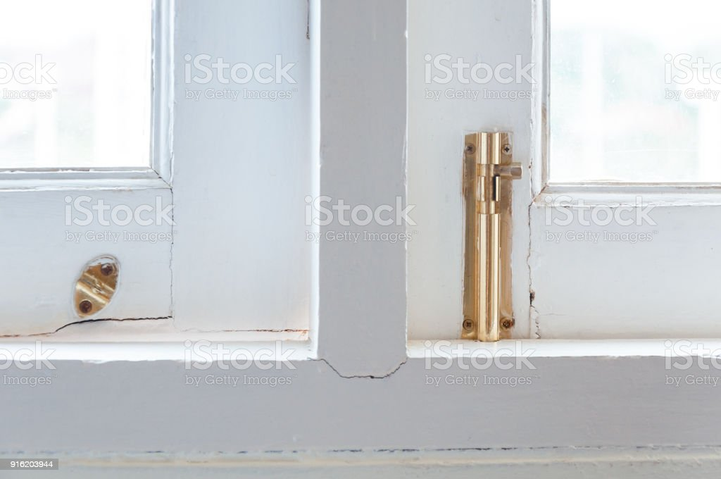Old gold hasp on old vintage greed wooden window stock photo