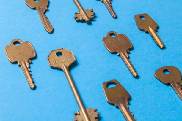 altes gold oder kupfer schlüssel auf blauem grund. - schlüssel dekorationen stock-fotos und bilder