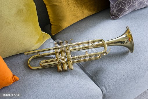 old golden trumpet lying on grey sofa and cushion