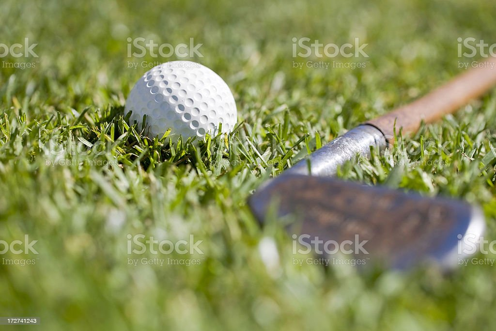 A ground level view of an old golf ball and iron on the grass