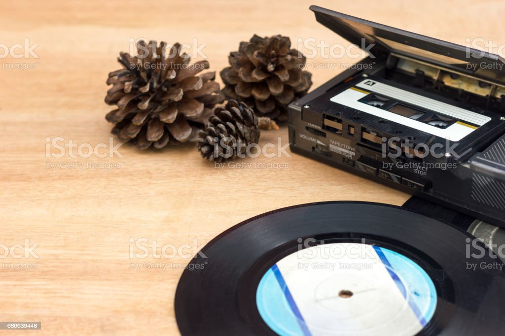 Old gramophone record, Old portable taps player, Cassette, Dry pine flower on wood background. royalty-free stock photo