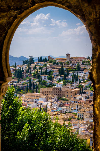 old granada seen from an arched window in the alhambra - spain stock pictures, royalty-free photos & images