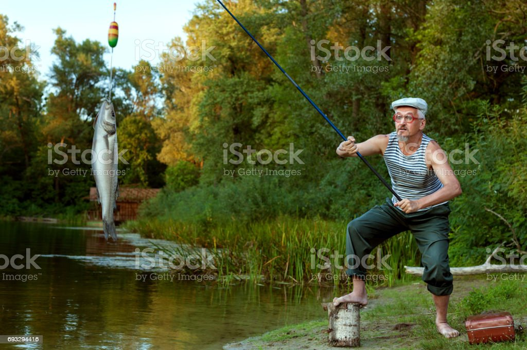 Old grandfather on a fishing trip. stock photo