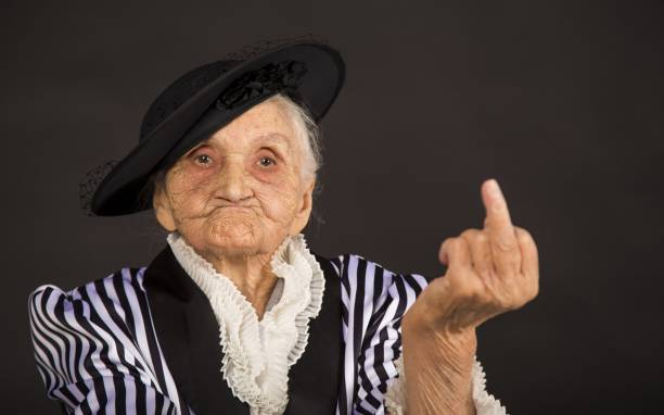 Old grandma in a white-black striped jacket Stylish old woman in black hat gesturing stock pictures, royalty-free photos & images