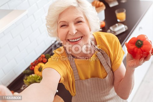 Old grandma making selfie toothy smile, holding a red pepper . Indoor, studio shoot, kitchen interior