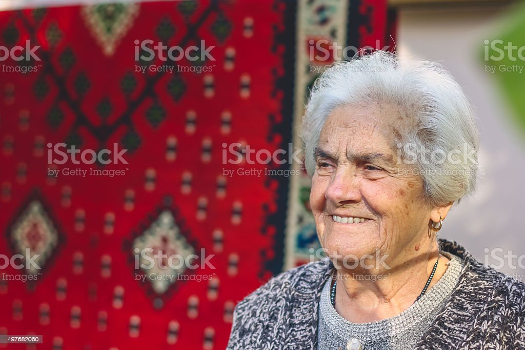 old grandmother standing and smiling stock photo