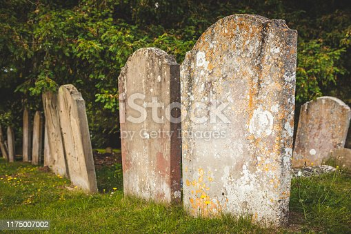 A row of old gravestones worn by erosion in a grass covered cemetary