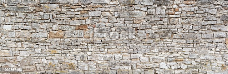 Panorama - Old gray wall of rough, many small, rectangular hewn natural stones