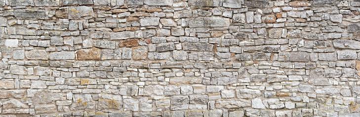 Panorama - Old gray wall of rough, many small, rectangular hewn natural stones