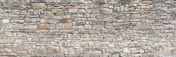 Old gray natural stone wall Panorama - Old gray wall of rough, many small, rectangular hewn natural stones stone material stock pictures, royalty-free photos & images